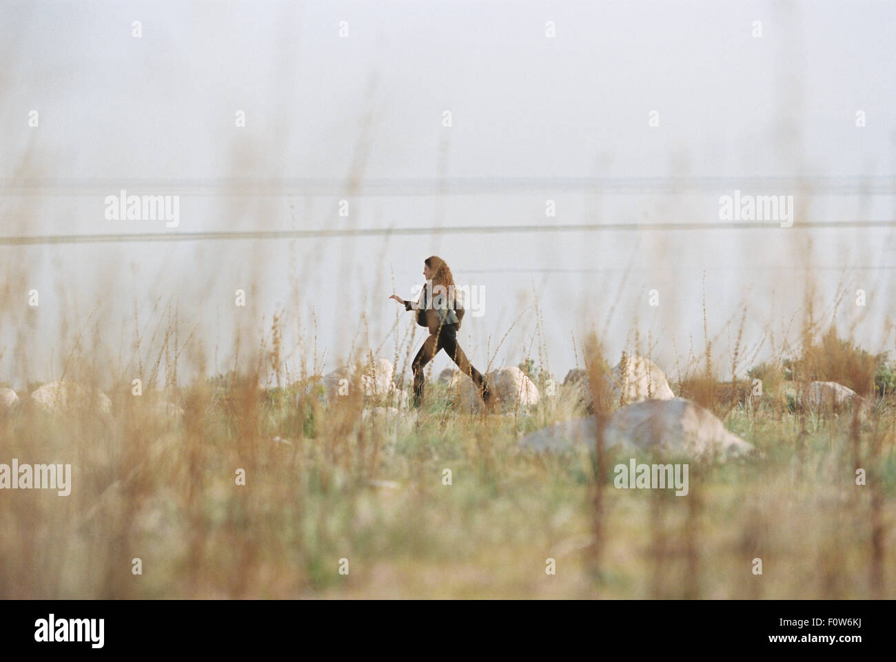 A woman striding across the grass past rocks along the shore of a lake. - Stock Image