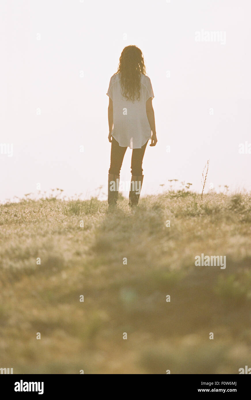 Woman with long curly hair standing looking towards the horizon. - Stock Image