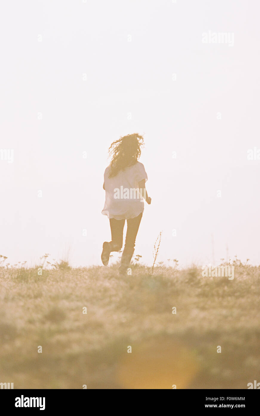 A woman running with her long hair fanning out behind her. - Stock Image