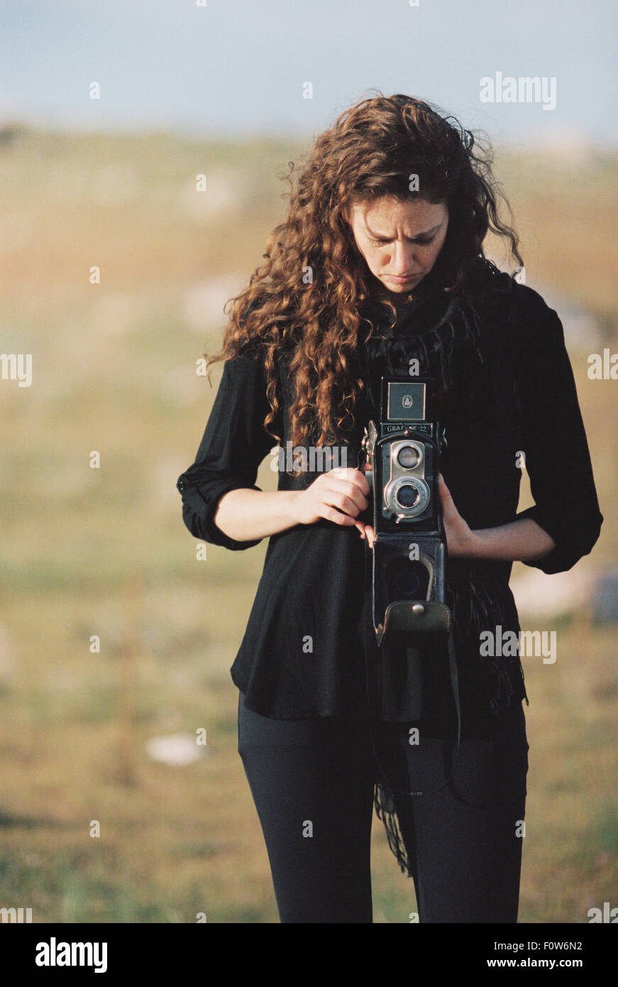 A woman taking a picture with an old fashioned medium format camera. - Stock Image