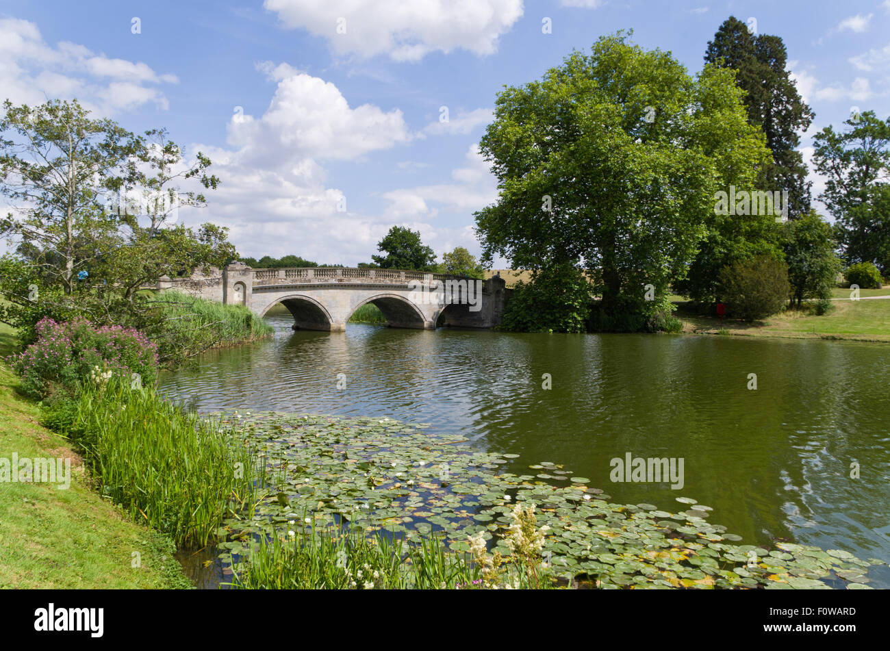A three arched stone bridge going over the lake at Compton Verney House, Warwickshire, UK - Stock Image