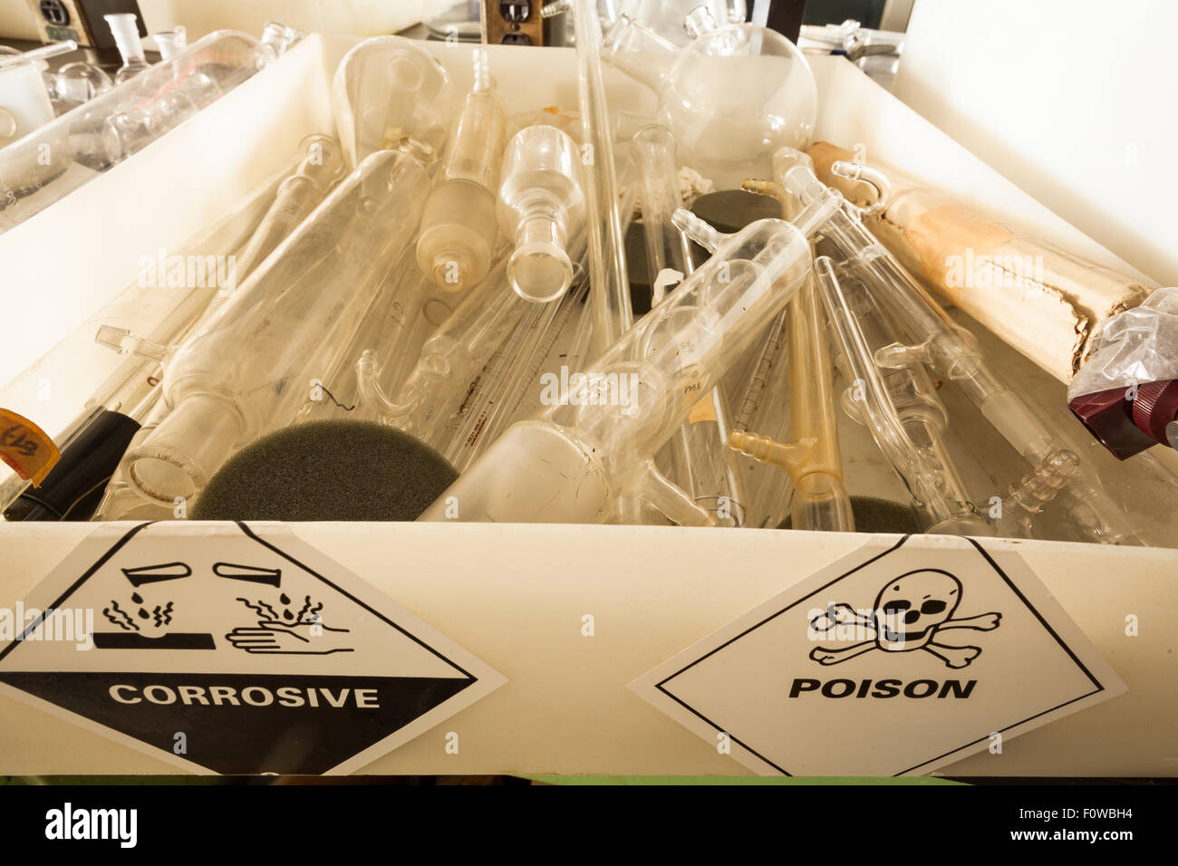 A box of chemistry glassware, with corrosive and poison stickers. - Stock Image