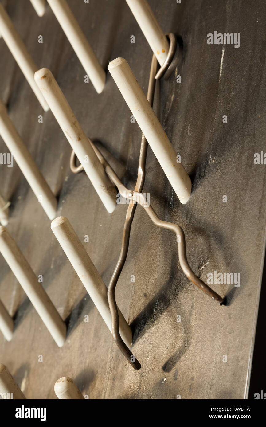 Chemistry tongs hanging on a peg board. - Stock Image