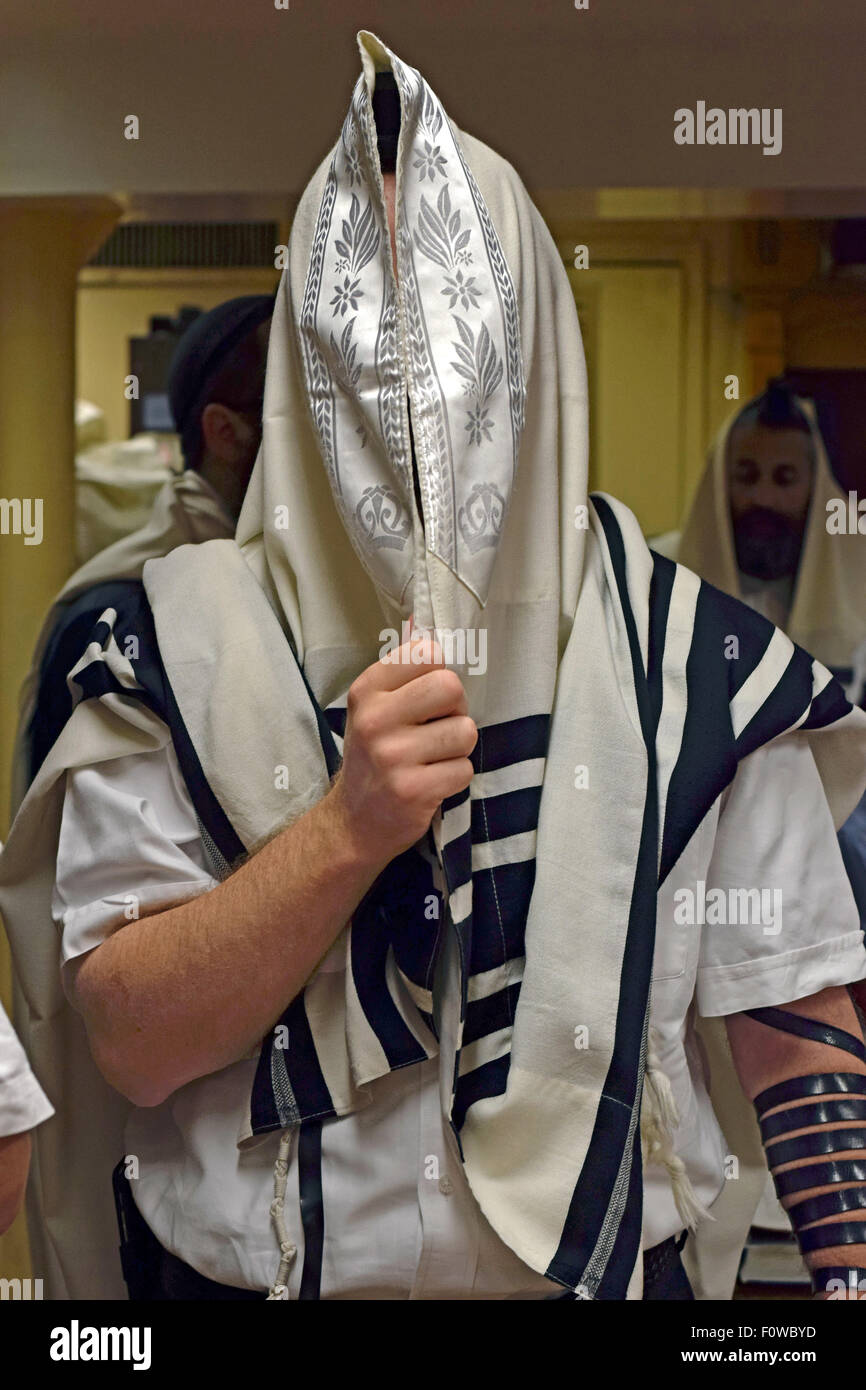 A religious Jewish man in fervent prayer at a synagogue in Crown Heights, Brooklyn, New York - Stock Image