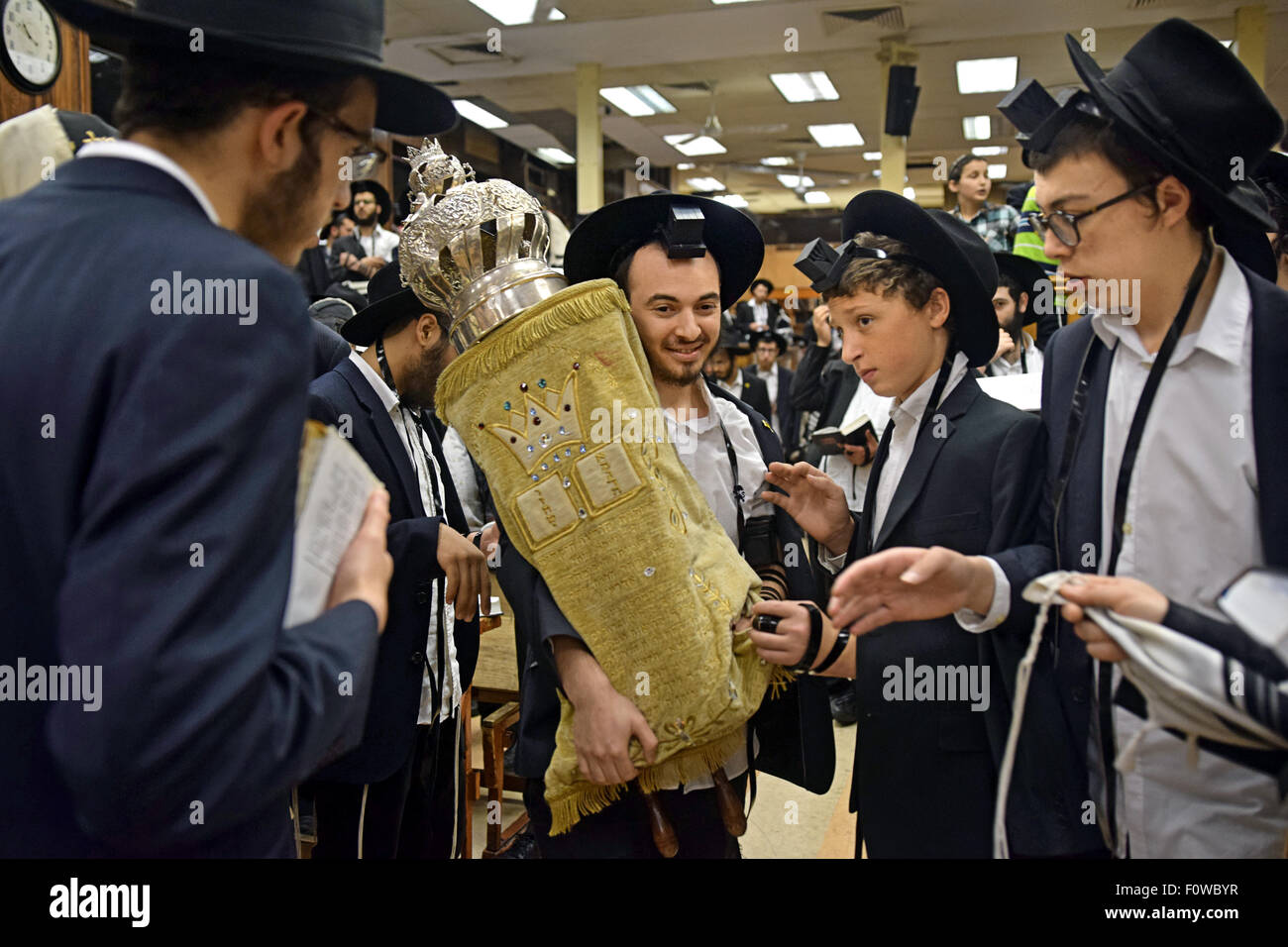 A young man returns a Torah to the Holy Ark after a reading at morning services in a synagogue in Crown Heights, - Stock Image