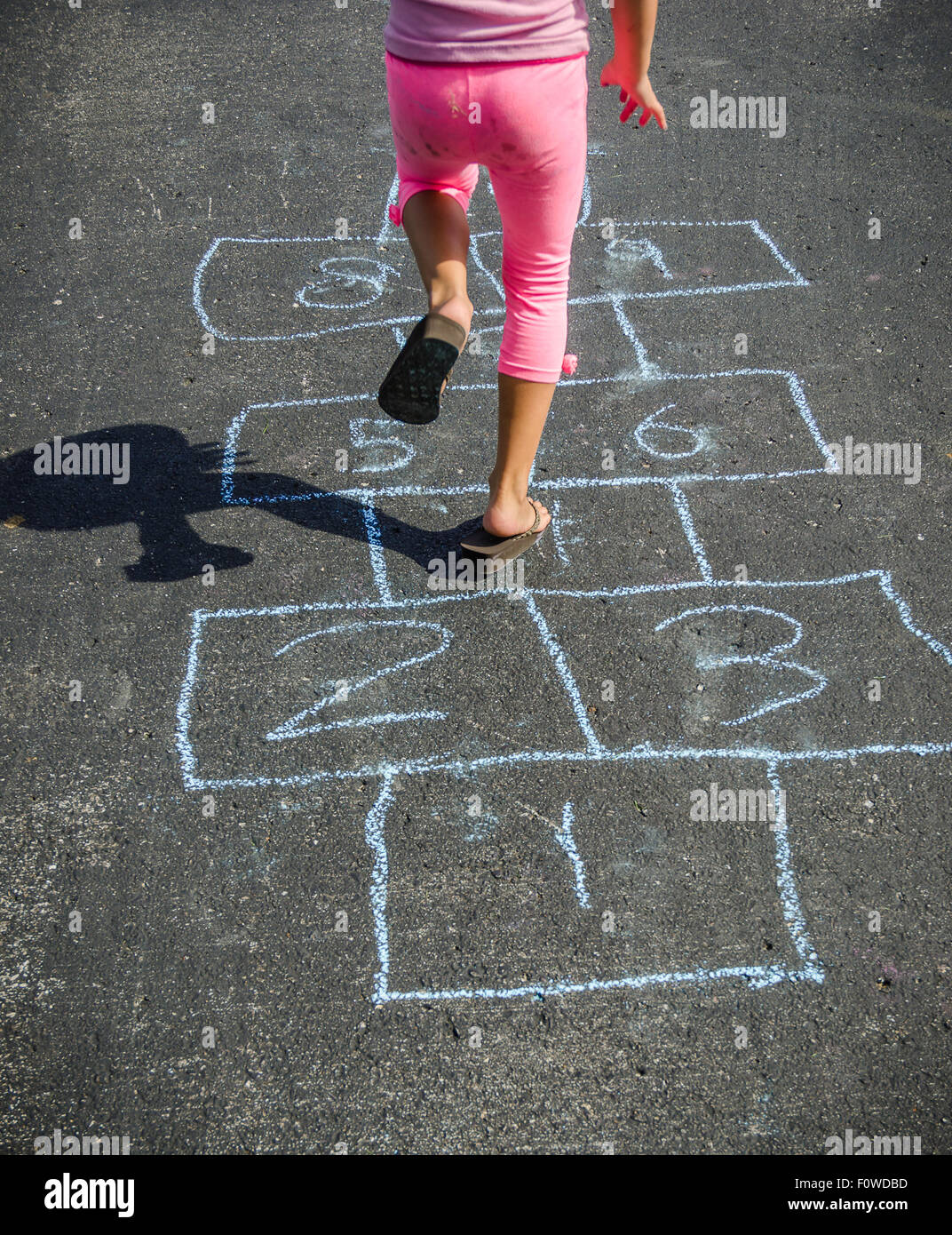 Young Girl Hopping While Playing a Game Outdoors on a Sunny Warm Day Wearing Pink Pants and Sandals - Stock Image