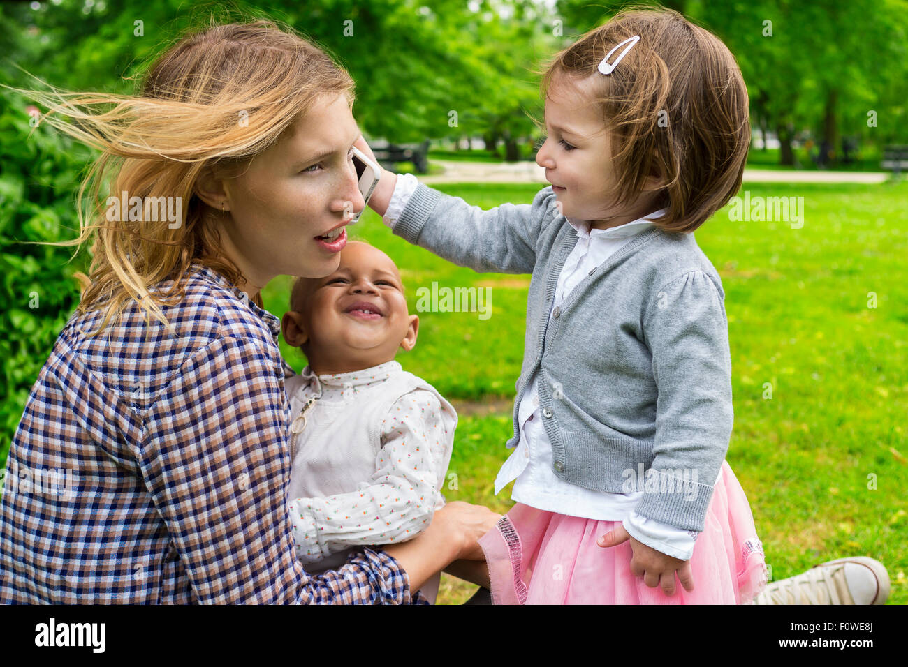 Cute toddler holding a smartphone to mother's ear - Stock Image