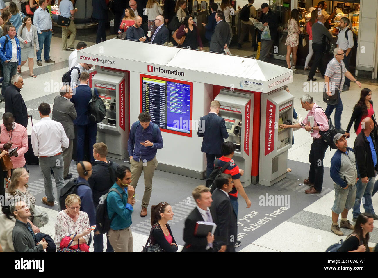 Rush hour commuters buying tickets by using the ticket machines on the concourse at Liverpool Street Station. - Stock Image