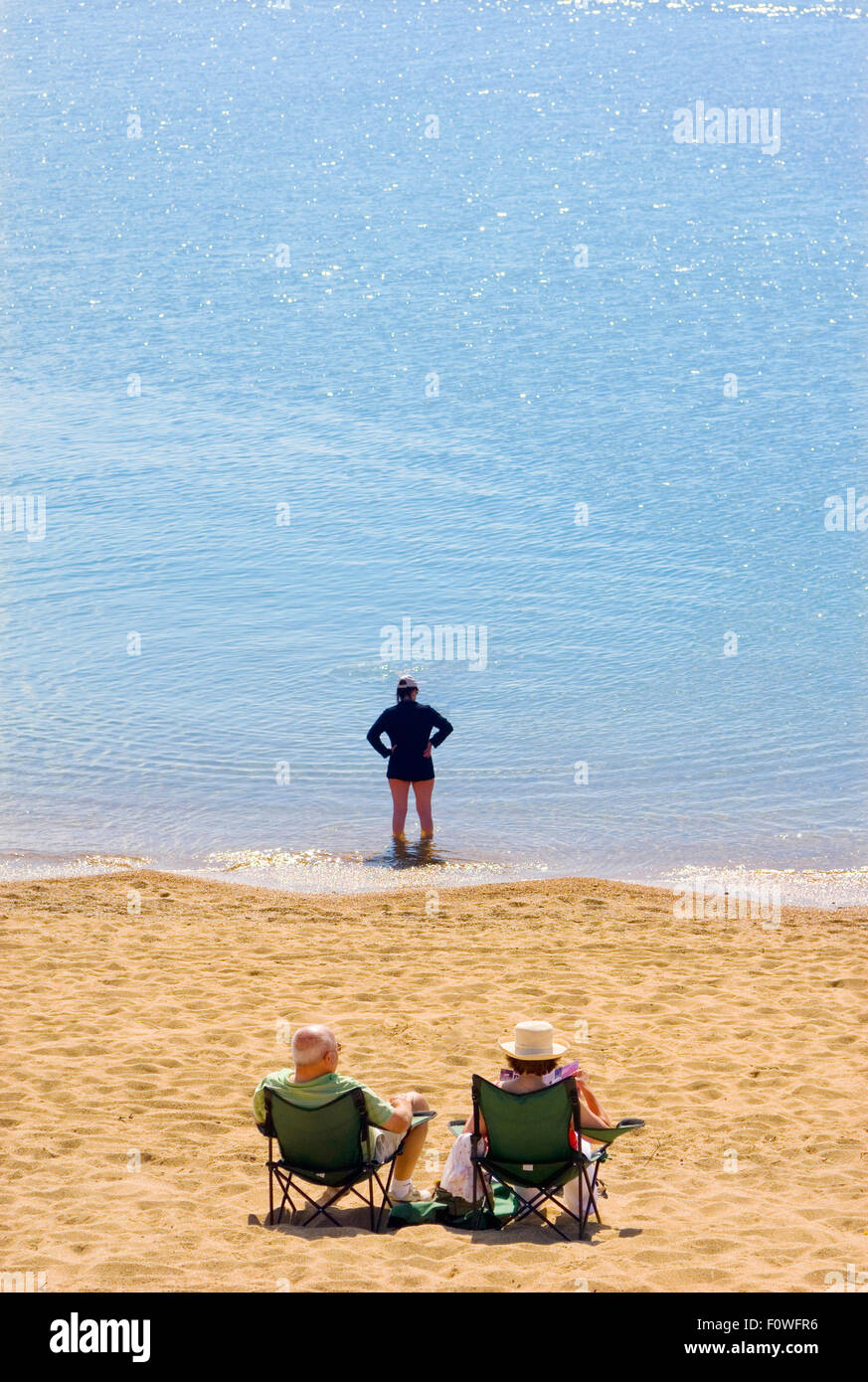 sunbathers on the beach in deck chairs and paddling in the blue sea. - Stock Image