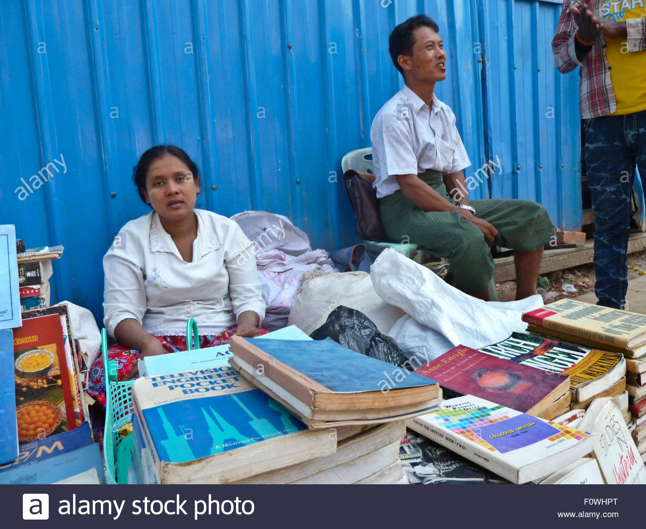 A female and male street bookseller seen sitting behind a table of used and second hand novels, paperbacks and books. - Stock Image