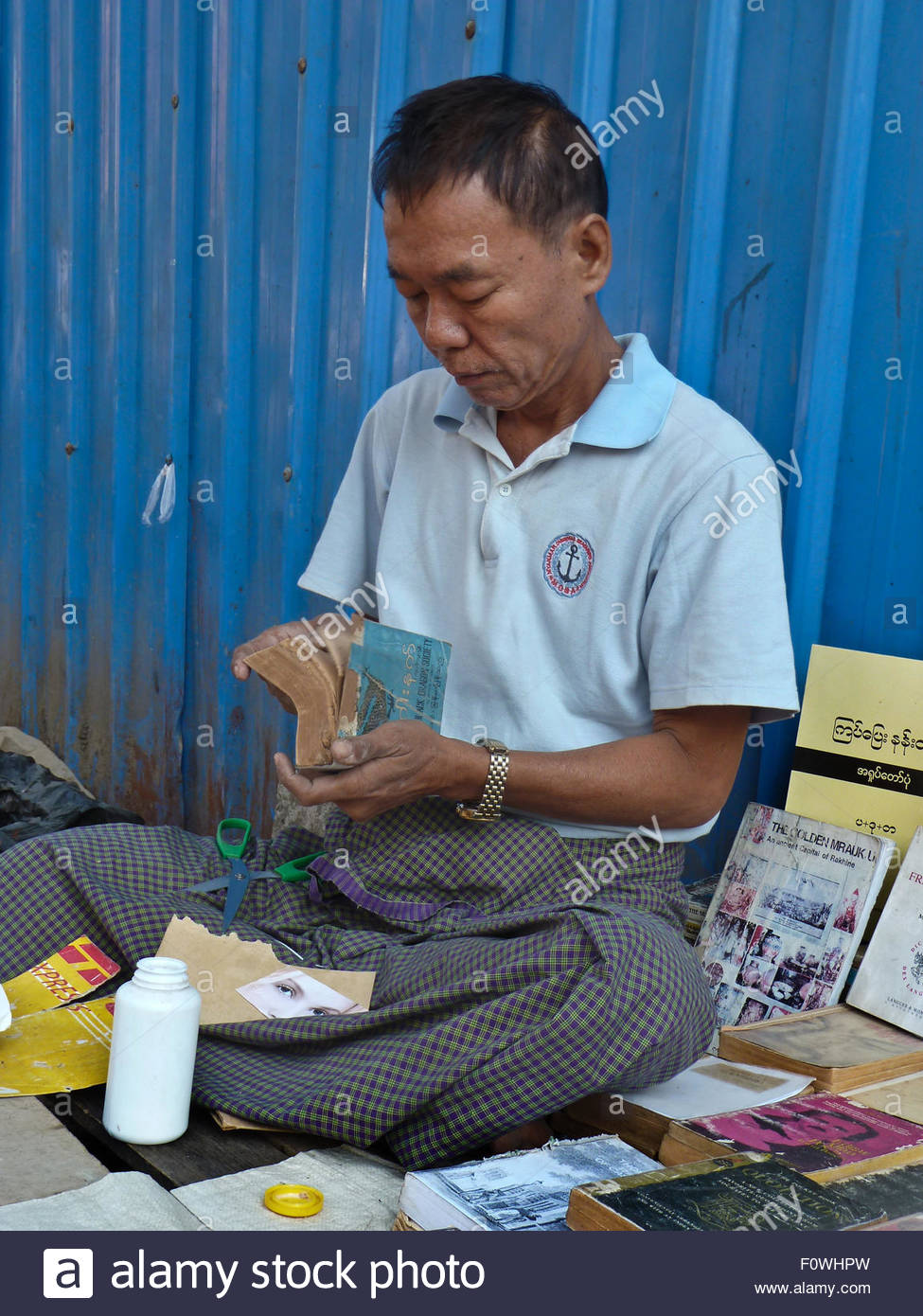 A street bookseller in Yangon, Myanmar (Burma) repairs a paperback while minding his display. Unlike neighboring - Stock Image