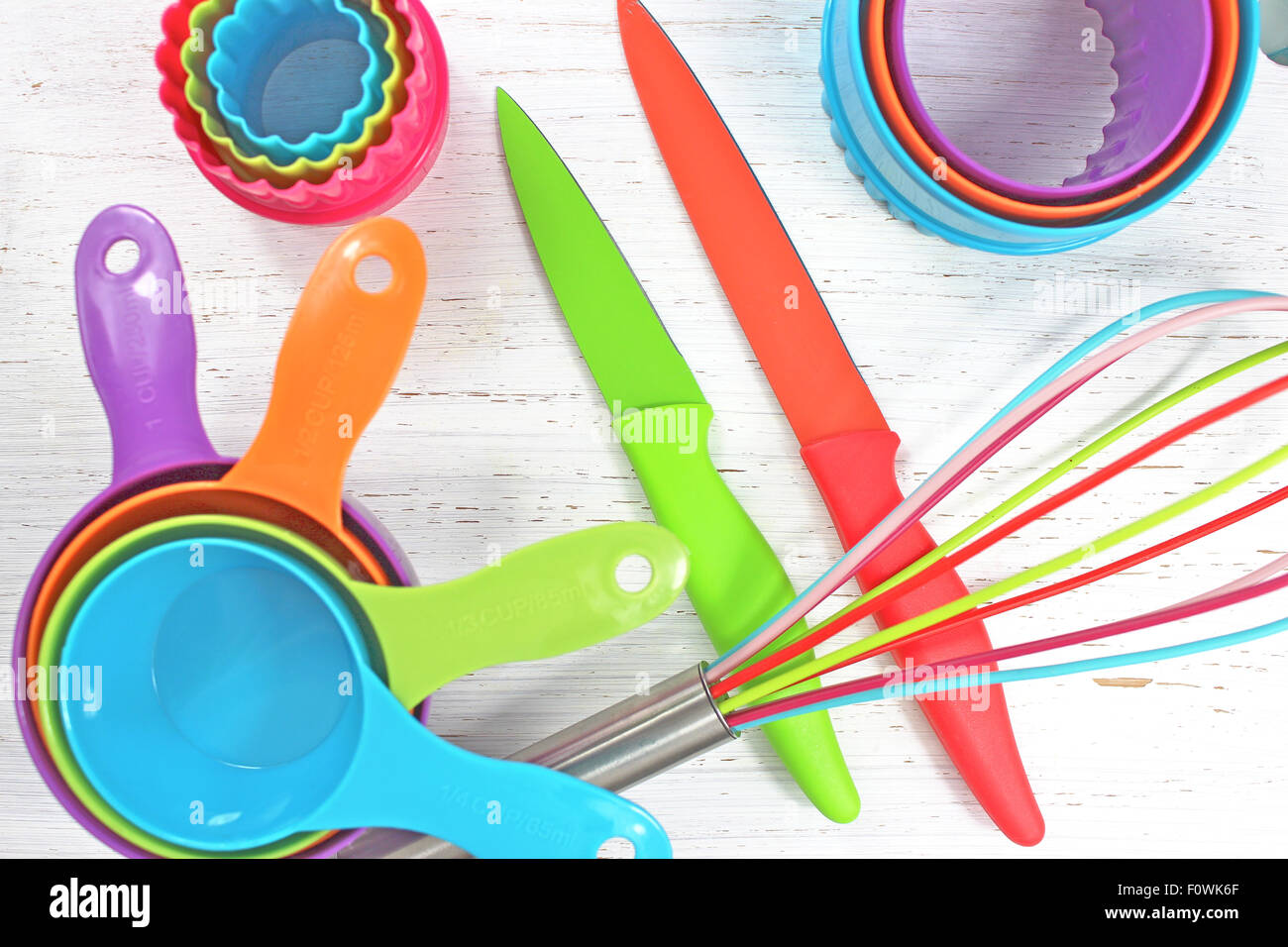 colorful kitchen utensils on white rustic background - Stock Image