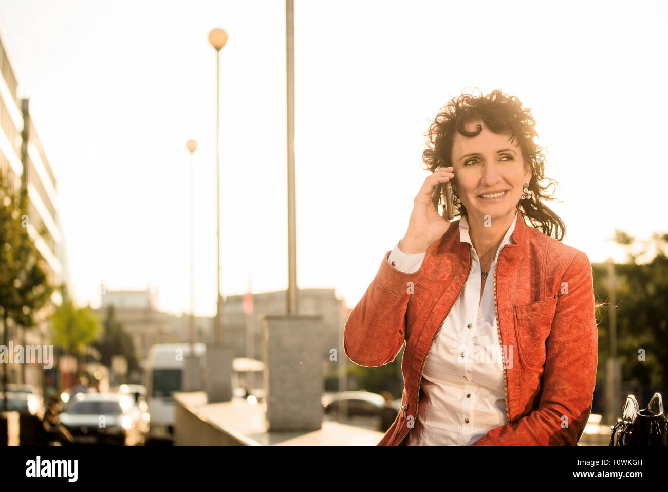 Senior woman in red jacket calling mobile phone while sitting in street at sunset - Stock Image