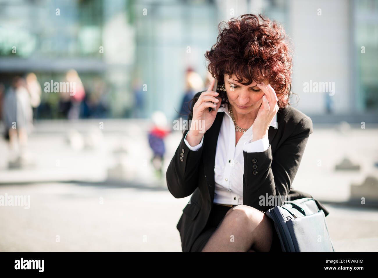 Senior business woman with headache calling phone outdoor in street - Stock Image