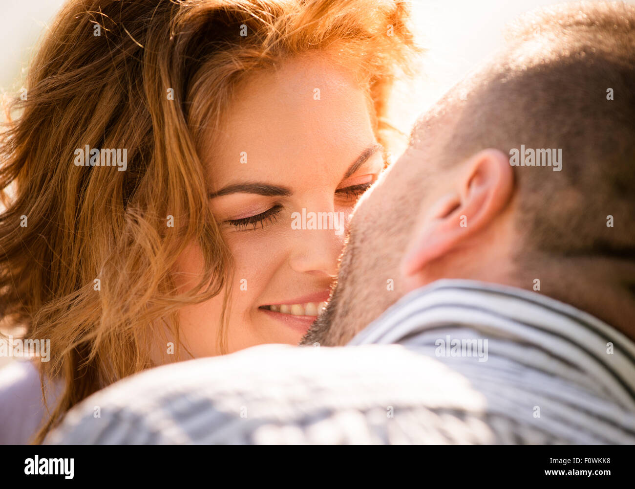 Candid close up photo of man kissing young smiling woman - Stock Image