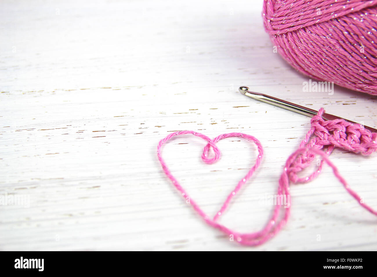 pink crochet background with yarn heart on white rustic wooden background with copy space - Stock Image