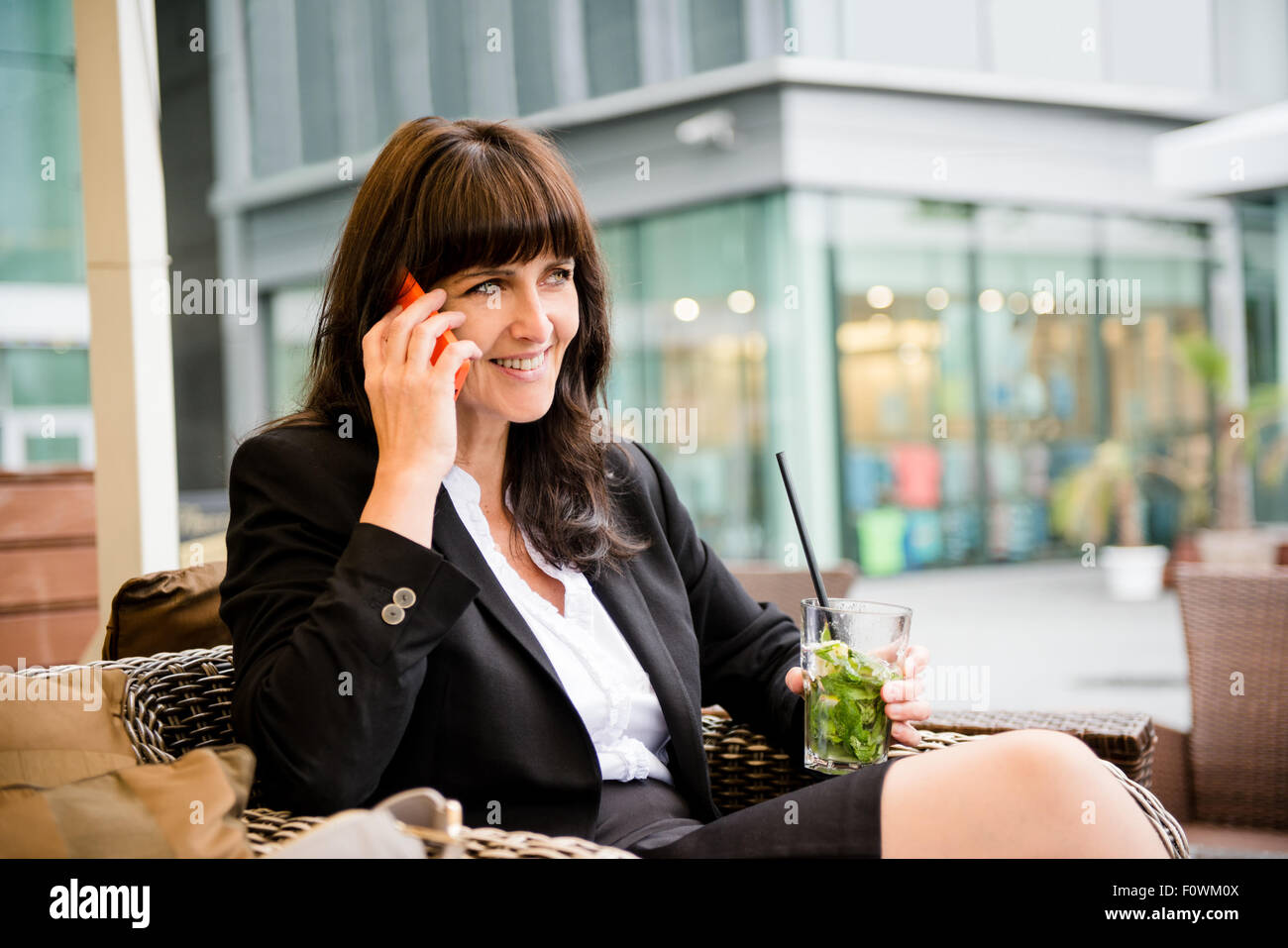 Senior business woman drinking mojito outdoor in street bar and calling phone - Stock Image