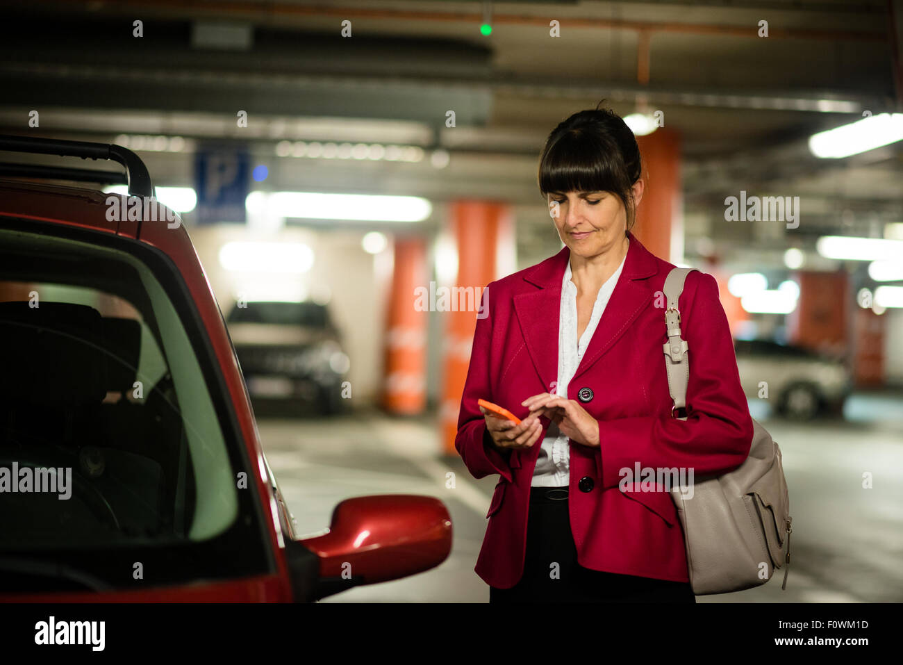 Senior business woman looking to her mobile phone while standing at her car - Stock Image