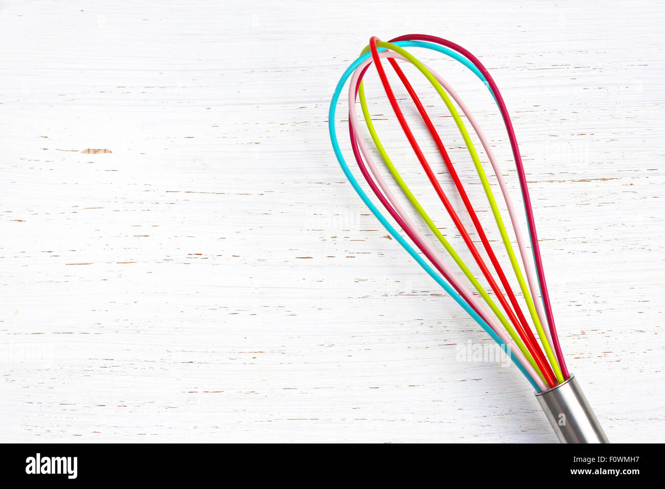 colorful whisk on white distressed wood chopping board. Kitchen/baking background. - Stock Image
