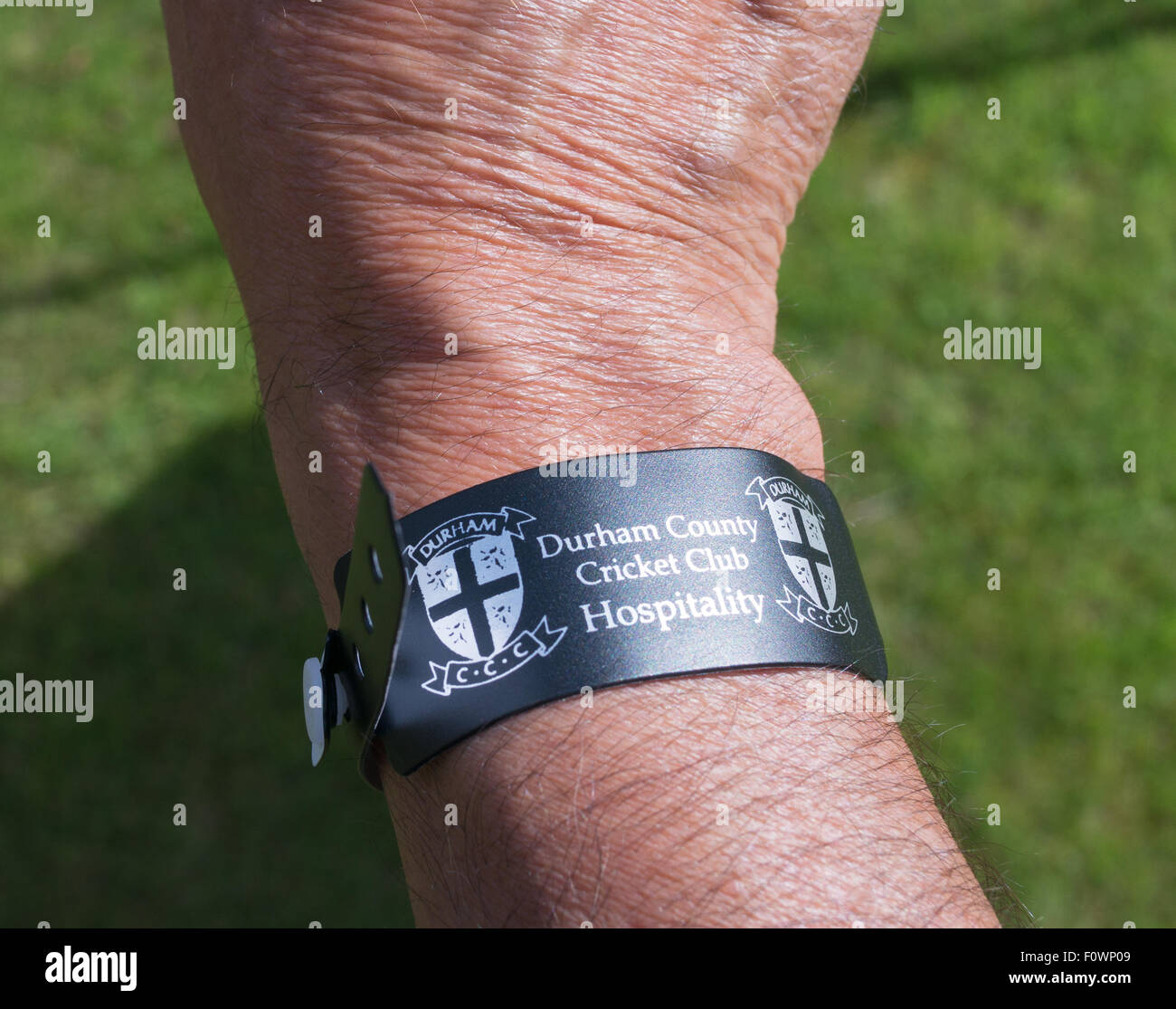 A man's forearm wearing a Durham County Cricket Club Hospitality wristband. - Stock Image