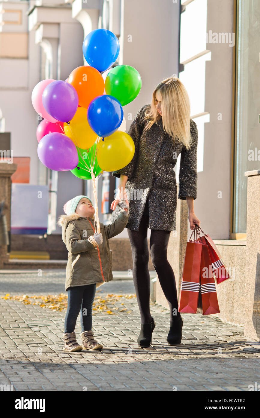 happy woman and little child with red shopping bag and air-balloons, walking on street - Stock Image