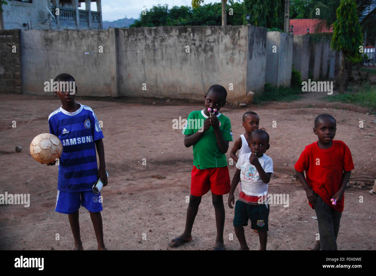 0460b0323 Nigerian boys with football uniforms, stand up for a portrait in a local  village at
