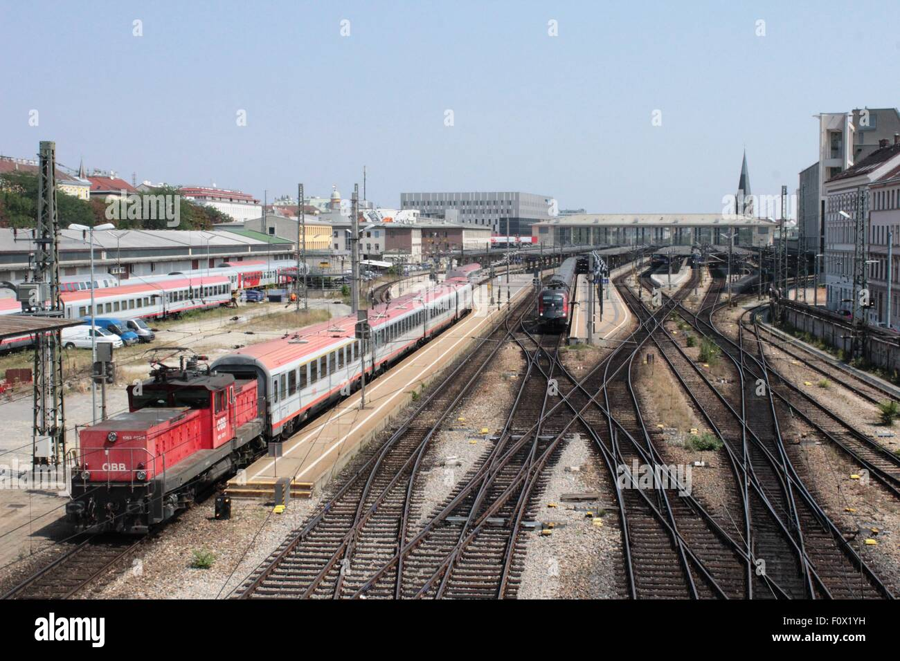 Railway track with trains at the entrance to Westbahnhof railway station, Vienna, Austria with electric loco shunting - Stock Image