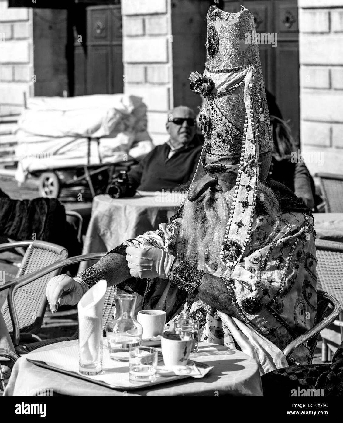 A costumed carnival goer has a coffee break near St. Marks Square - Stock Image