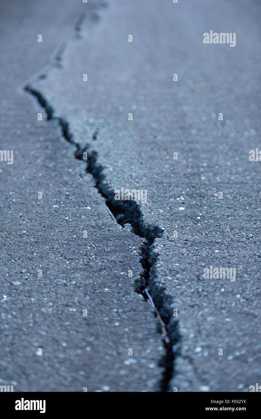 A long windy crack on a paved street. - Stock Image