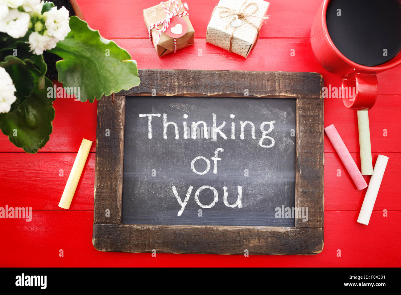 Thinking of You message written on a little chalkboard on a red wooden board - Stock Image