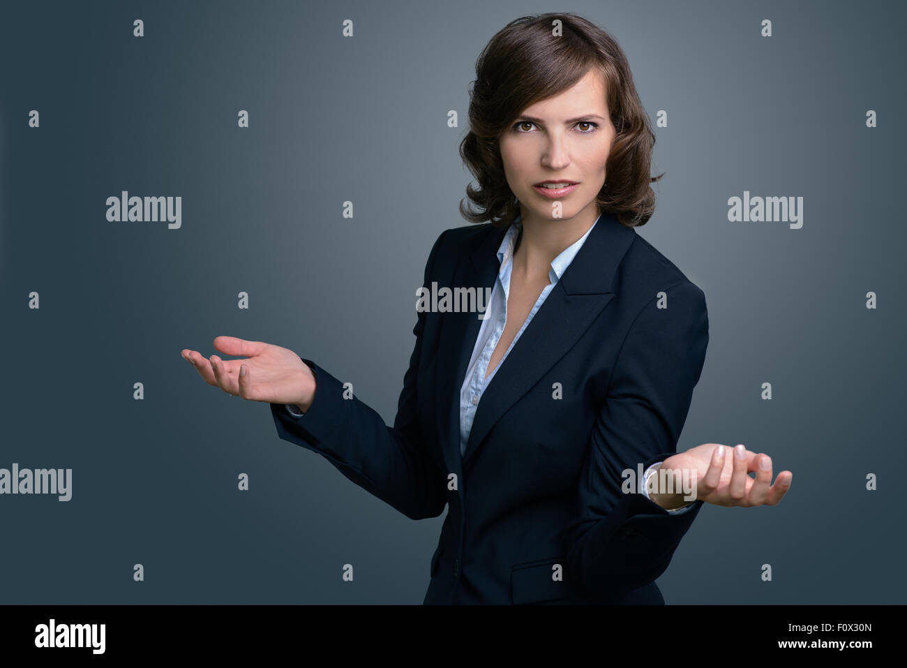 Half Body Shot of a Confused Young Businesswoman with Hands in the Air, Looking into the Distance Against Gray Wall. - Stock Image