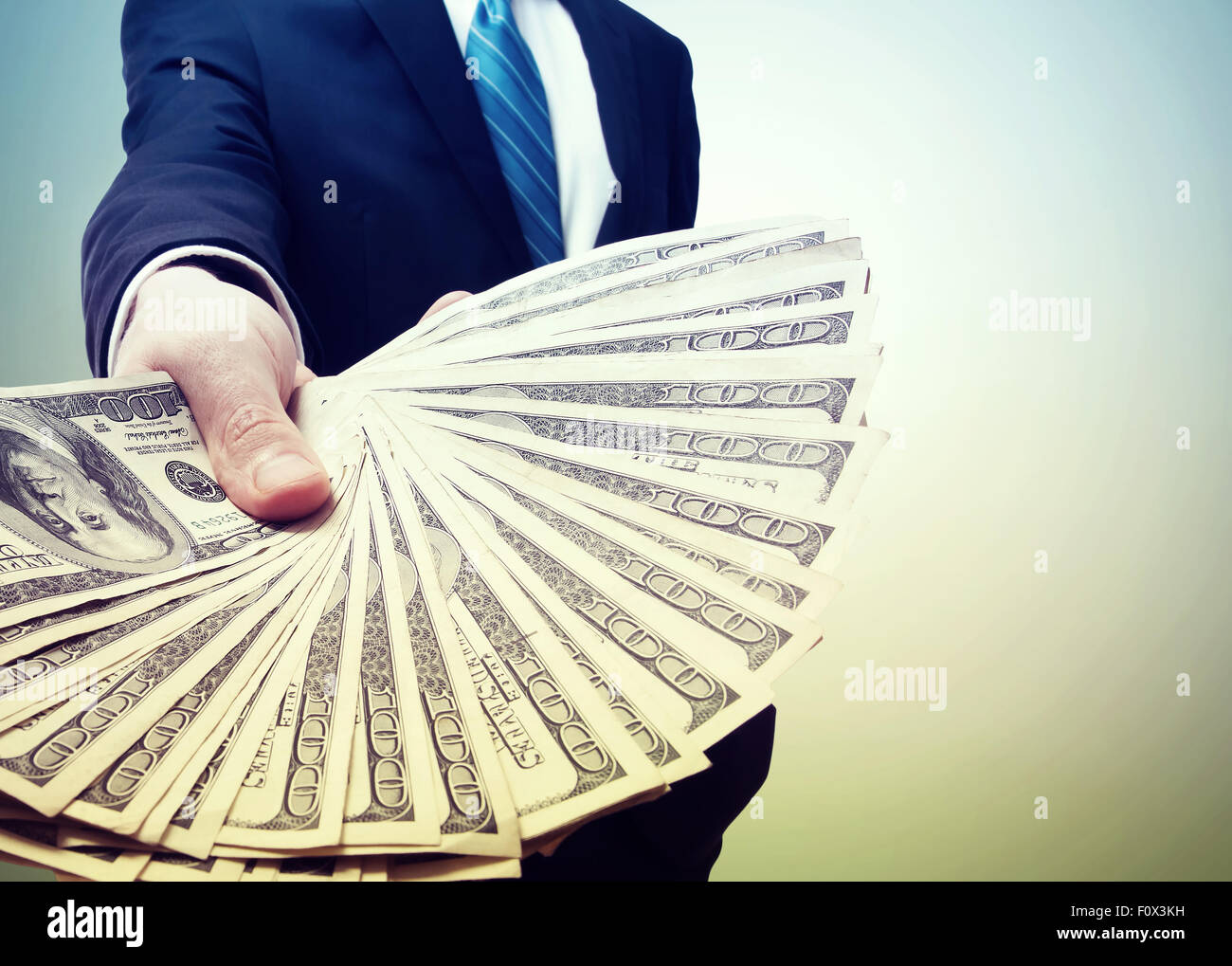 Business Man Displaying a Spread of Cash in Vintage Light - Stock Image