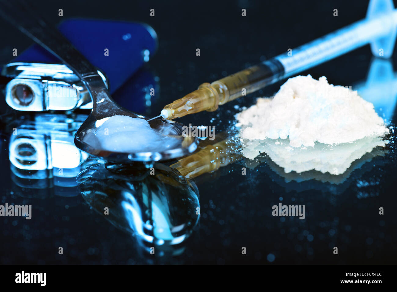 White powder on mirror with lighter spoon and syringe - Stock Image