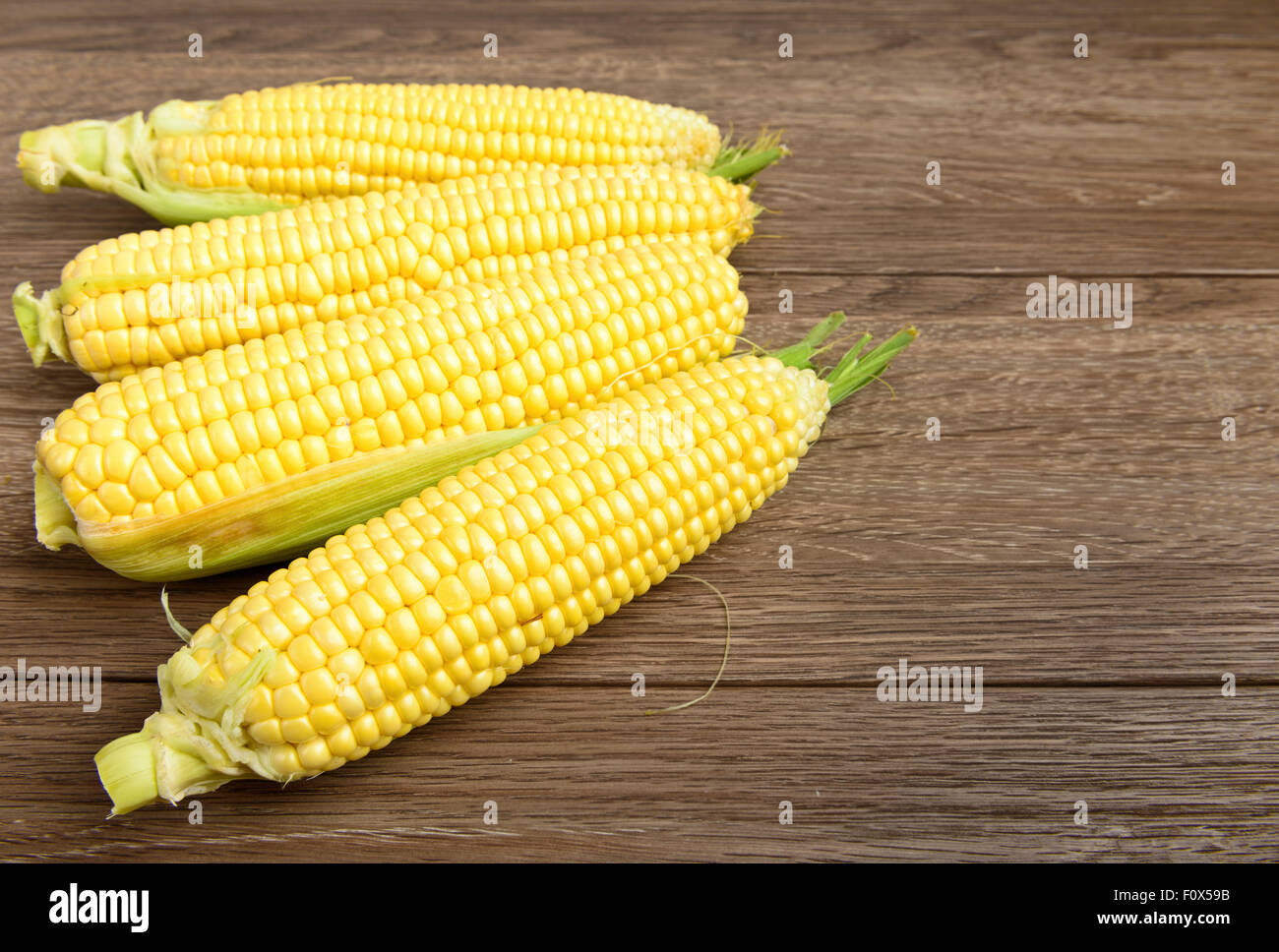 Fresh raw corn on wooden table Stock Photo