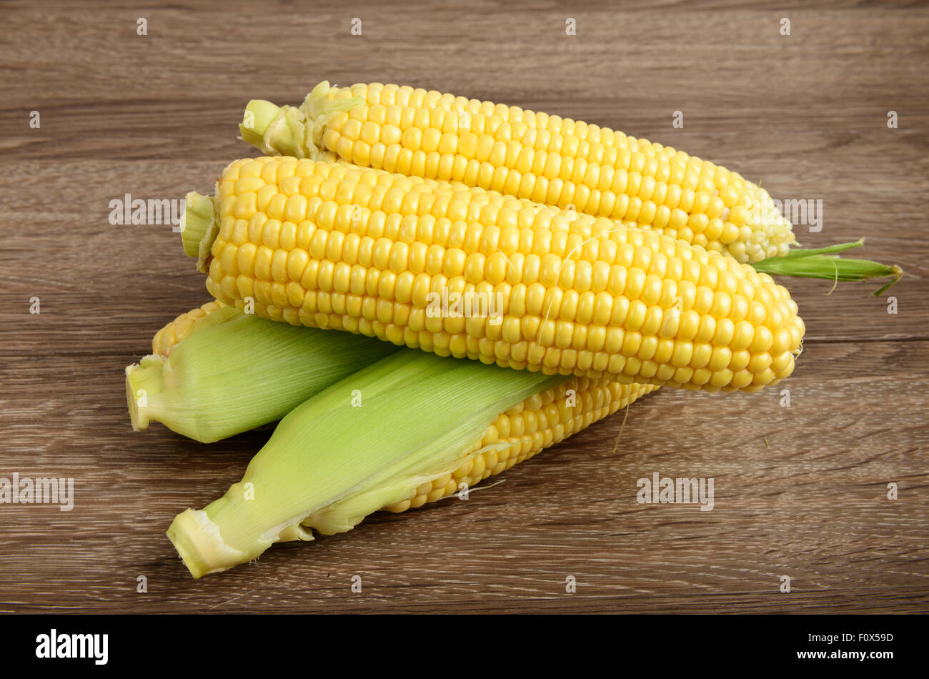 Fresh raw corn on wooden table - Stock Image