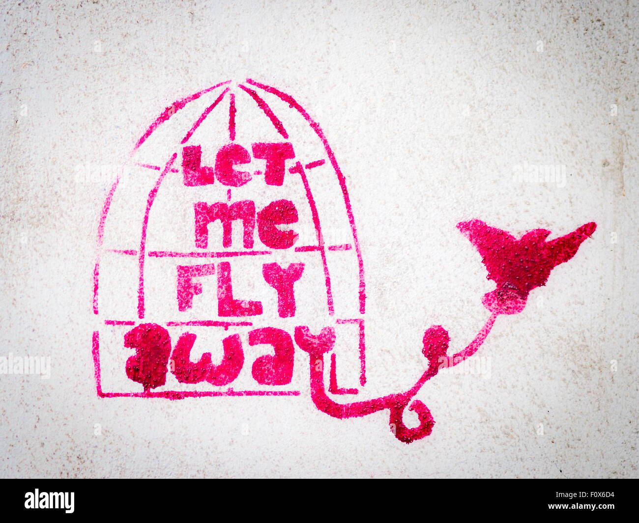 Pink stencil graffiti with bird leaving a cage - Stock Image