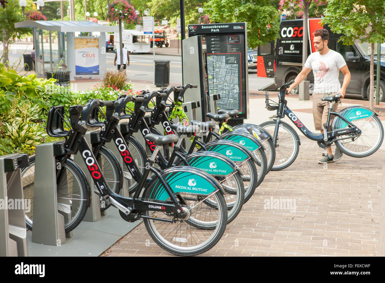 A young man restocks a CoGo docking station with bicycles at the Sensenbrenner Park station in Columbus, Ohio. - Stock Image