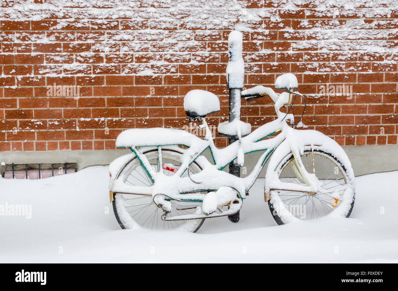 A bicycle leaning against a brick wall and covered in deep fresh snow after a snowstorm in Montreal, Canada - Stock Image