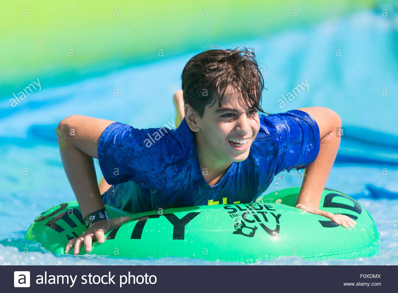 An exuberant young boy smiling as he enjoys a ride on a giant water slide during a Slide the City event in North Stock Photo