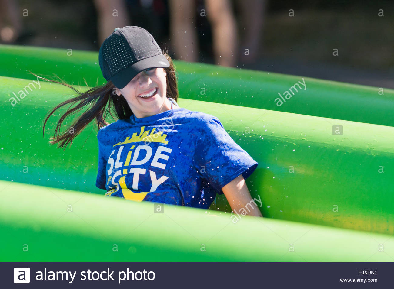 Close up of a teenage girl smiling as she enjoys a ride down a giant water slide during a Slide the City event in Stock Photo
