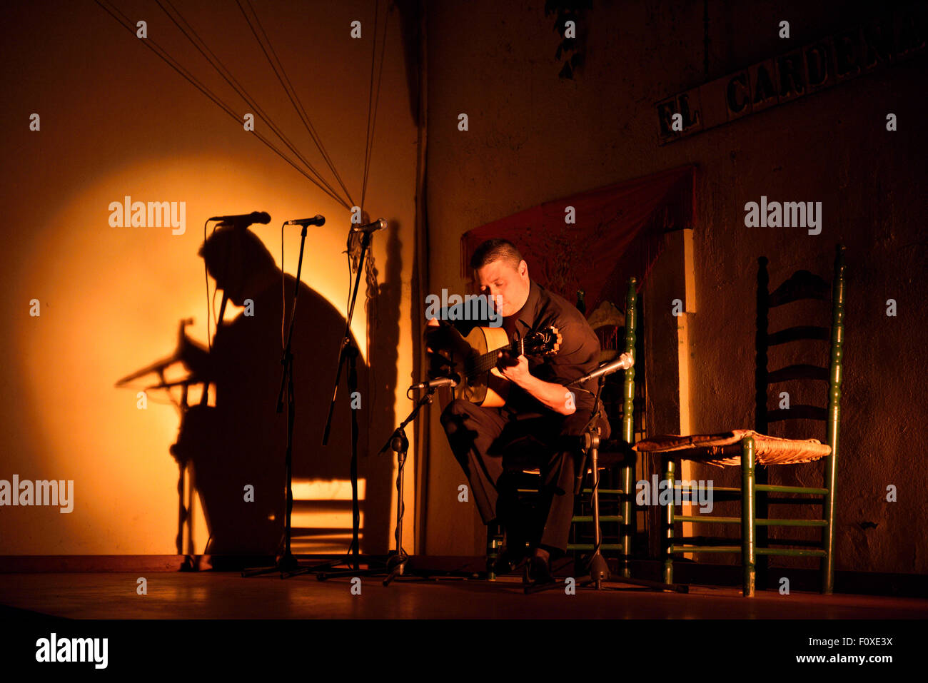 Solo Flamenco guitarist in spotlight on stage at night in Cordoba Spain - Stock Image