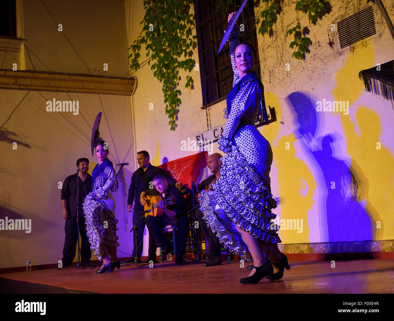 Spotlit female Flamenco dancers on stage with fans and shadows on wall in an outdoor courtyard in Cordoba Spain - Stock Image