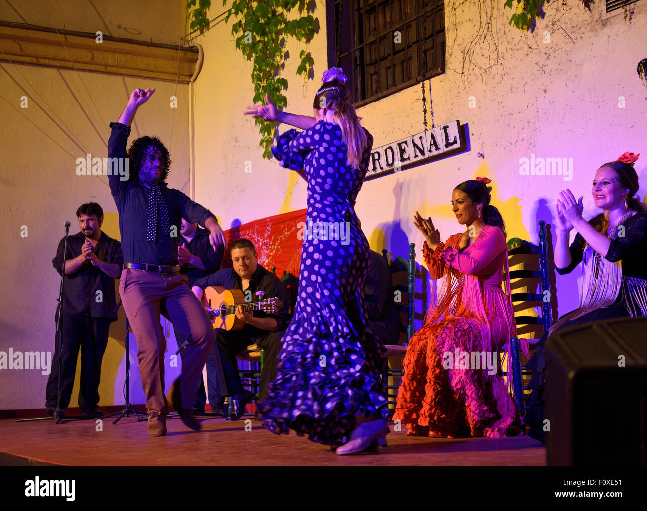 Couple of Flamenco dancers with women clapping on stage at night in an outdoor courtyard in Cordoba Spain - Stock Image