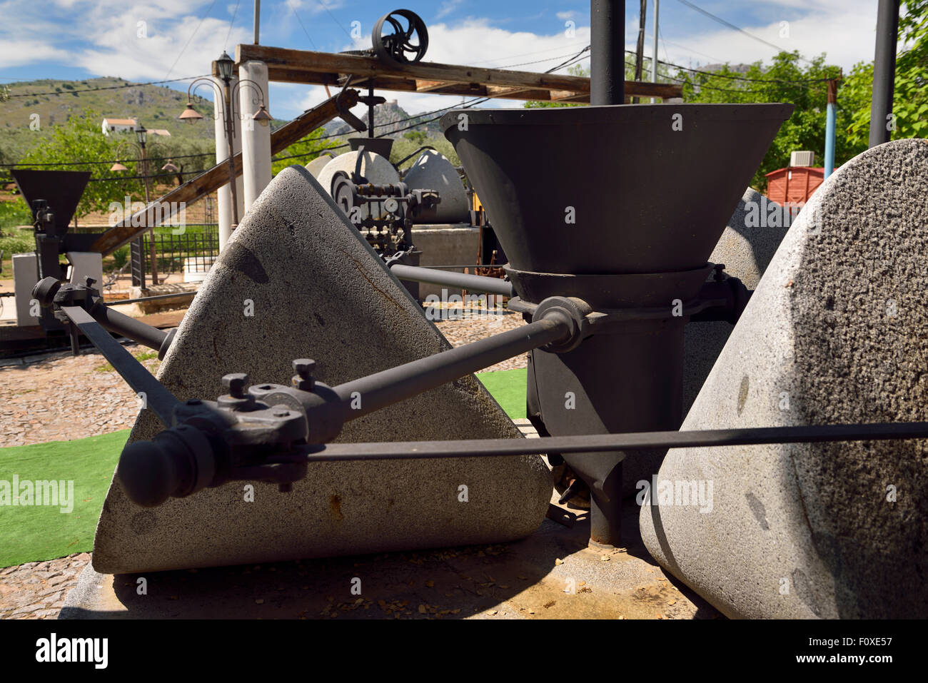 Large granite Millstones of Olive press machinery outside at Nicol's Hostel Restaurant near Luque Spain - Stock Image