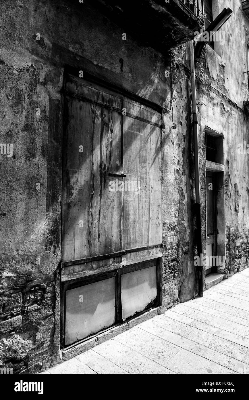 vintage wooden door spotlit by sunlight, black and white, Besalu, Spain - Stock Image