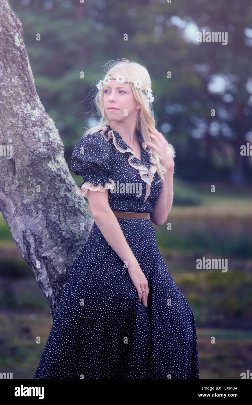 a blonde girl in a floral dressl is leaning against a tree - Stock Image