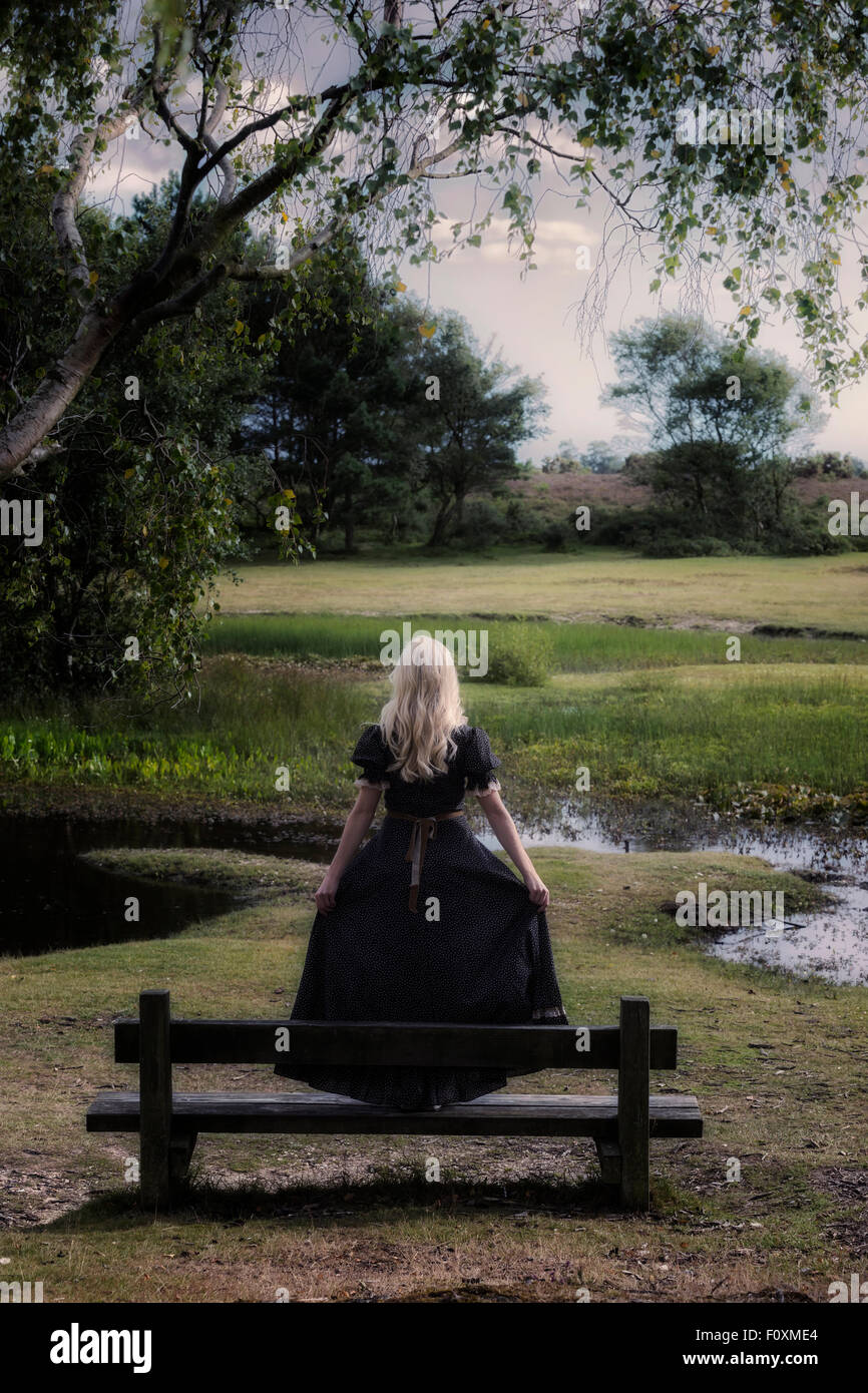 a blonde girl in a floral dressl is standing on a bench at a pond - Stock Image
