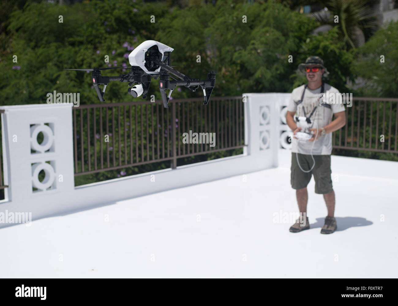 Man controlling DJI Inspire Drone quadcopter a  commercial and recreational unmanned aerial vehicle for aerial photography - Stock Image