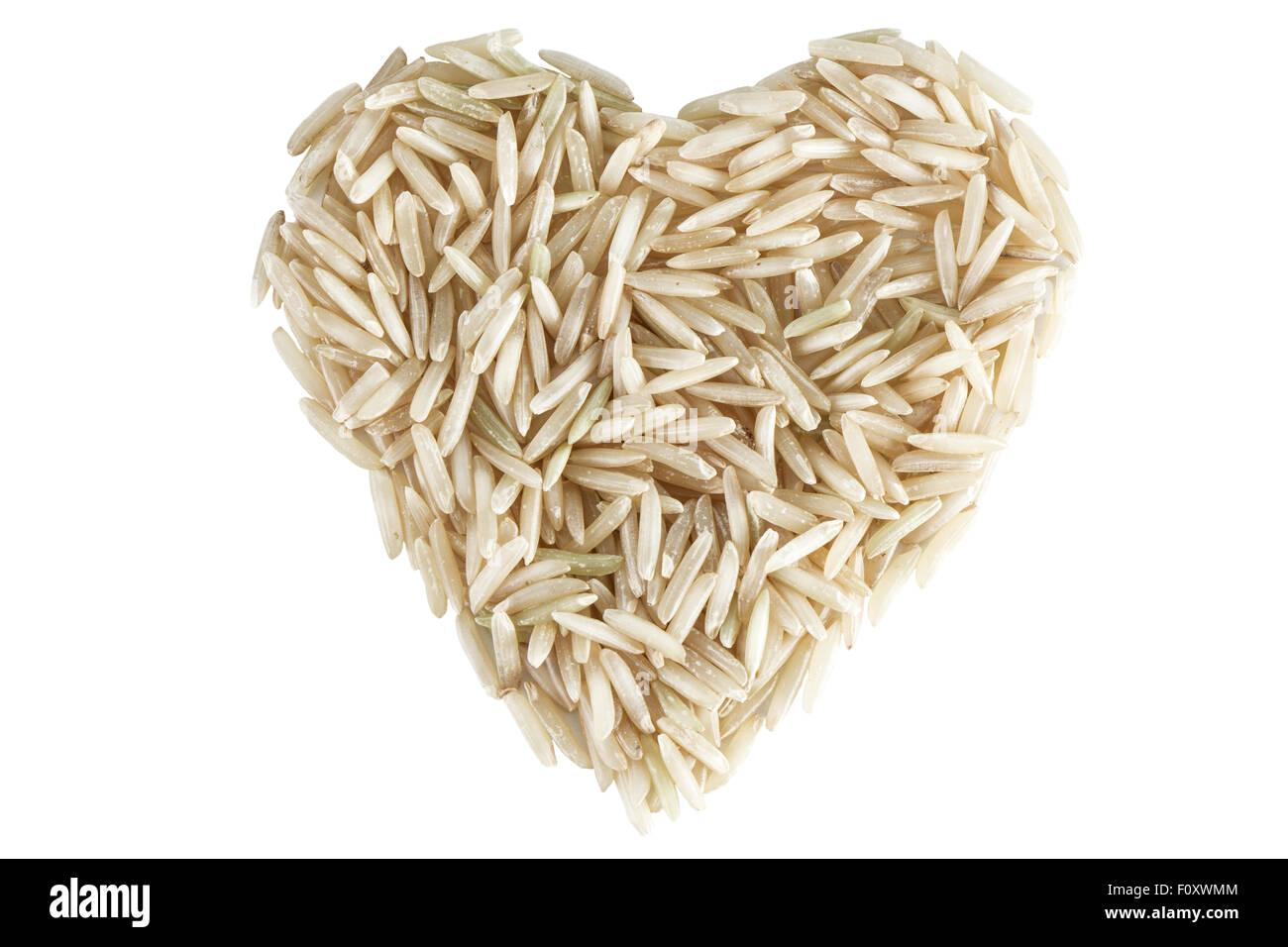 Heart shape made of wholegrain basmati rice viewed from above, isolated on white background. Stock Photo