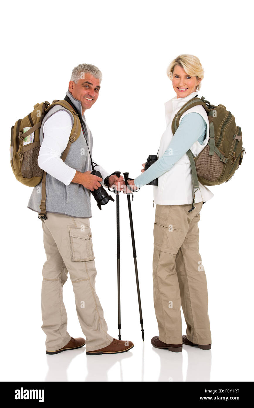 happy mid age couple with backpacks looking back - Stock Image
